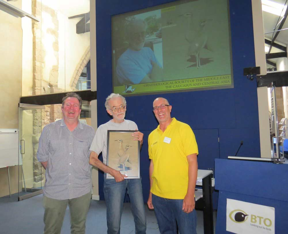 Plate 6. Peter Cowan receives a framed picture of his favourite Sandgrouse front cover.